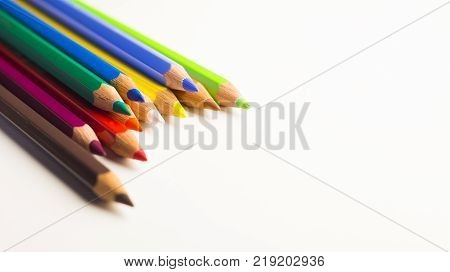 Colored pencils laying on top of each other on a white background
