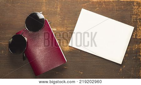 blank passport with a white blank postcard and black pair of glasses on a wooden background