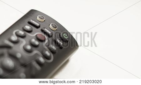TV remote control with focus on and off button on a white background