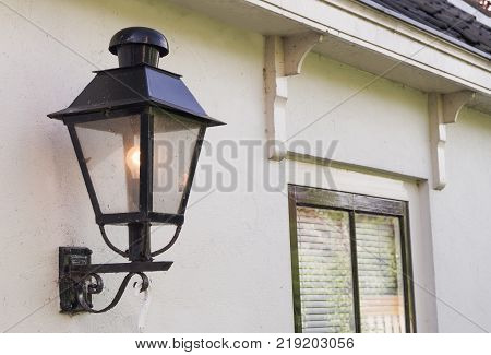 a black outdoor electrical lantern on a white wall