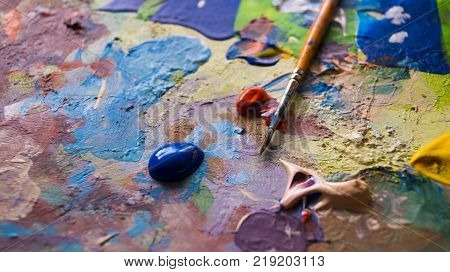 a paint brush placed up top of the photo with drops of wet acrylic paint dropped next to the brush on a used paint palette surface.