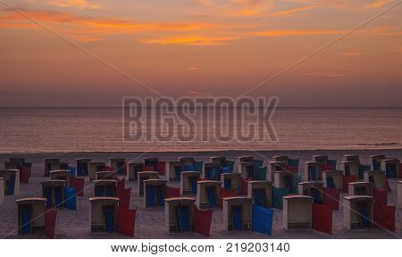 Small beach hut houses on the beach while the sun is setting behind the horizon on a summer evening sunset