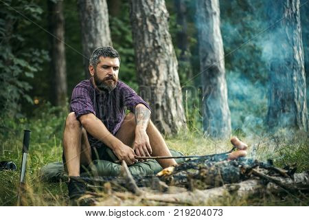 Hipster Hiker Roast Sausages On Stick On Fire In Forest