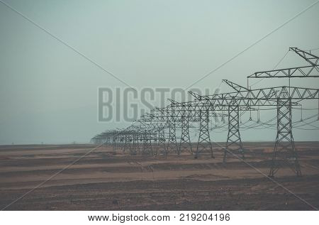 Electricity distribution stations. Electric energy transmission. Ecology eco power technology concept. Power line towers in desert on blue sky background. Global warming climate change.