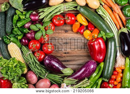 Top view of assortment organic vegetables ( potato carrot onion tomato zucchini eggplant corn pepper bell garlic beans) on wooden background with copy space.