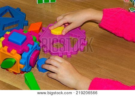Closeup Of Child's Hand Taking Bright Mosaic Parts. Learning Colors At Home. Toddler Boy In A Stripe