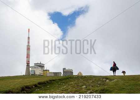 Balkan mountain Bulgaria - August 17 2016: Weather station radio tower (opened 1966) and man riding donkey on the highest peak (Botev) of Balkan Mountains