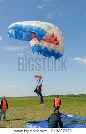 Yalutorovsk, Russia - May 24, 2008: Competition of parachutists on landing accuracy on sport airdrome. Parachutist woman missed by landing point