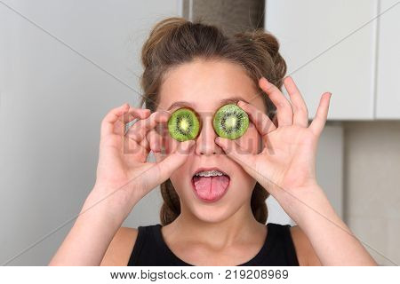 girl teenager with his tongue hanging out and kiwi instead of glasses