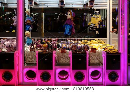 BERLIN, GERMANY - DECEMBER, 05: The close-up of dolls and stuffed animals of a colorfully lit doll-claw slot machine at a Christmas market on December 05, 2017 in Berlin.