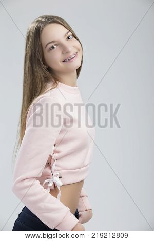 Dental Concepts. Portrait of Happy Teenage Female With Teeth Brackets. Posing with Smile Against White.