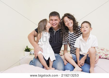 Portrait of Happy Caucasian Family with Two Kids Posing Together Embraced and Smiling Happily. Girl Kissing Her Father.Horizontal Image Orientation