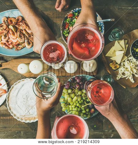 Holiday celebration table setting with food. Flat-lay of friends hands eating and drinking together. Top view of people having party, gathering, celebrating with rose champaign, square crop