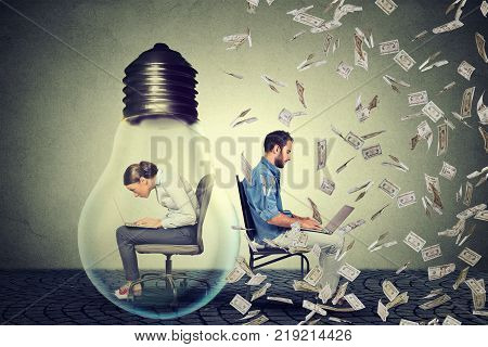 Woman sitting inside electric lamp using working on computer in corporate office next to young entrepreneur man under money rain. Company employee vs startup concept. Pay compensation difference idea