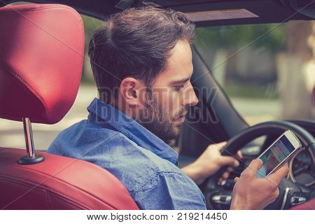 Man using cell phone texting while driving. Risky reckless driver concept