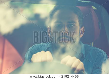 shocked scared funny looking young driver in the car. Human emotion face expression. Front window view of Inexperienced anxious driver concept