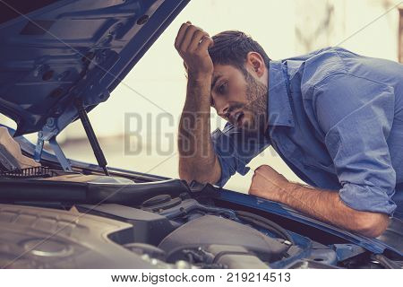 young stressed man having trouble with his broken car looking in frustration at failed engine