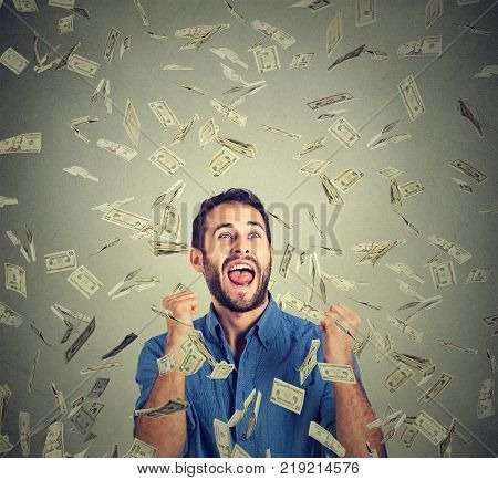 Portrait happy man exults pumping fists ecstatic celebrates success screaming under money rain falling down dollar bills banknotes isolated gray background with copy space. Financial freedom concept