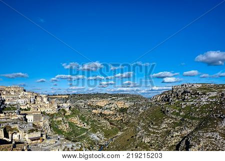 A city on a rocky outcrop and a complex of cave dwellings carved into the mountainside poster