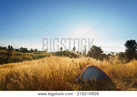 outdoors camping grass highlands mountain in the Sunset.outdoors camping highlands mountain.Orange tent on a hill above the river. The concept of freedom and adventure. Sunlit meadow at dawn. Symbol of a new day.