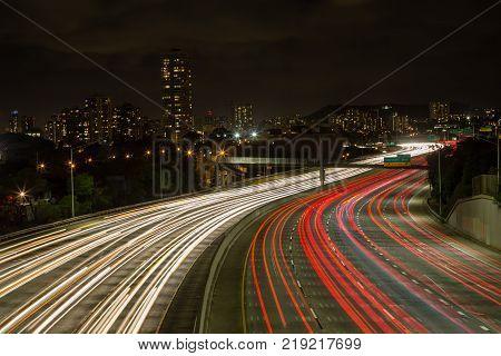 Light trails of vehicles on the Kapiolani exit to the motorway looking towards lights of Waikiki Oahu Hawaii along a winding multi-lane motorway