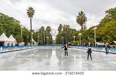 SEVILLA SPAIN - DECEMBER 15 2017: Ice skaters having fun on skating rink at traditional Christmas fair on Prado de San Sebastian in center of Sevilla city Andalusia Spain