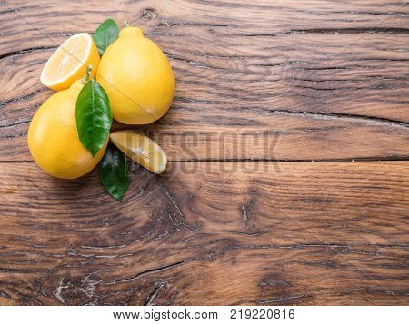Ripe lemons and lemon leaves on wooden background. Top view.