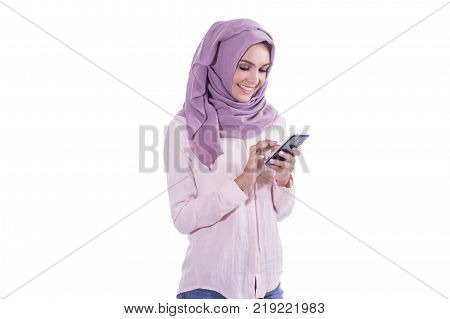 portrait of beautiful woman wearing hijab browsing internet on mobile phone isolated on white background