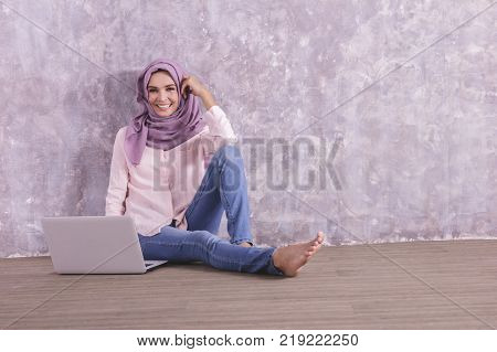 portrait of beautiful college student wearing hijab sitiing on the floor while studying on laptop with copy space