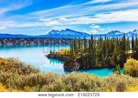 Abraham Lake in the Rockies of Canada. Turquoise smooth water reflects the sky. Warm sunny day in Indian summer. The concept of ecological and active tourism