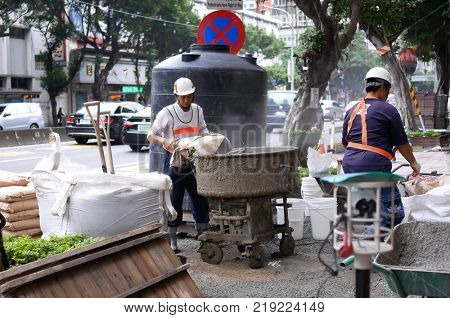 Taipei, Taiwan - December 03, 2017 : Motion of worker mixing cement for the preparation in construction site on road