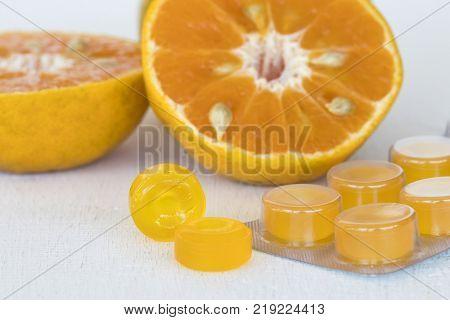 cough sore throat pastille pills from herbal fruit orange on background white