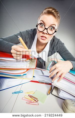 Administration workaholism clerk corporation concept. Crazy woman in office. Young angry lady at desk doing paperwork.
