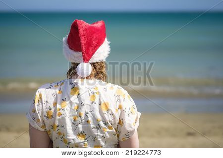 Teenage girl wearing Christmas santa hat at the beach looking out to sea