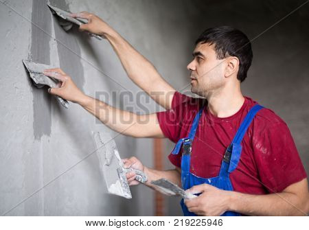 Collage worker with four hands makes repairs smears on wall putty