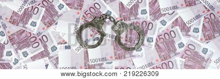Handcuffs on five hundred euros background. Financial crime, dirty money and corruption concept - 500 money bills and dirty steel handcuffs