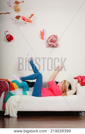 Mess at home household duties disorganization concept. Woman lying on sofa pelted clothes