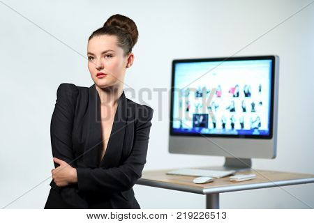 Young woman in black jacket stands with her hands clasped on background of computer desk and computer