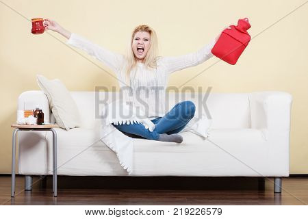 Happy woman showing ways to get rid of fever holding hot water bottle and hot drink in mug sitting relaxing on couch.