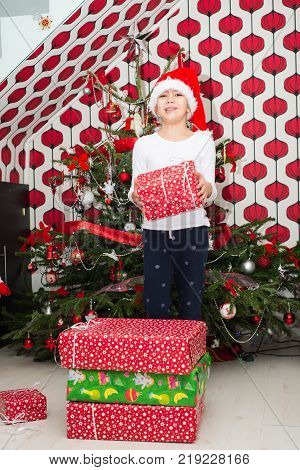 Happy Girl Holding Christmas Gifts In Front Of Christmas Tree