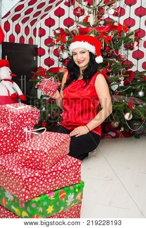 Cheerful Woman Holding Little Christmas Gift In Front Of Tree In Her Home