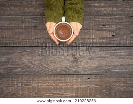 On a wooden table well-groomed women's hands hold a mug of hot cocoa