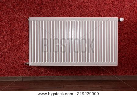 white heating radiator under in red room