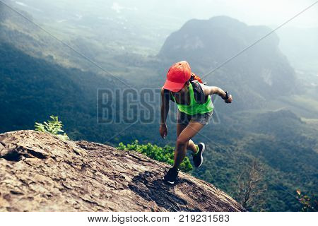 Young fitness woman running up to the mountain top