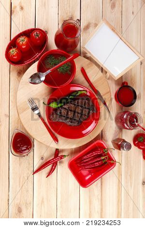 red theme lunch : fresh grilled bbq roast beef steak red plate green chili tomato soup ketchup sauce paprika small glass ground pepper american peppercorn modern cutlery served wooden plate table