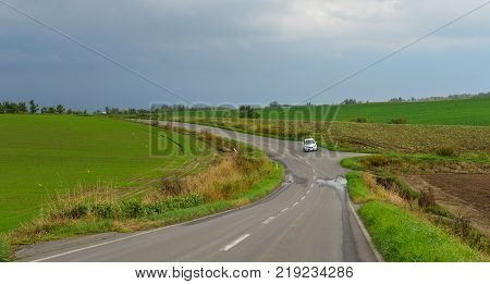 Hokkaido Japan - Oct 2 2017. A car running on rural road in Hokkaido Japan. Hokkaido is the second largest island of Japan and the northernmost prefecture.