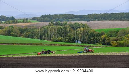 Hokkaido Japan - Oct 2 2017. Tractors working on the field in Hokkaido Japan. Hokkaido is the second largest island of Japan and the northernmost prefecture.