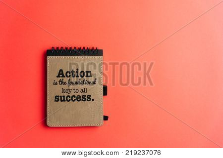 Lay flat of notebook with motivational quote on bubble-gum pink background. Conceptual, success