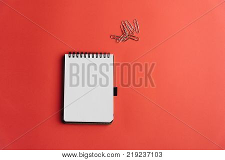 Lay flat of notebook with blank page and paperclips on bubble-gum pink background. Conceptual, success