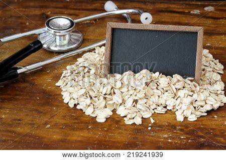 Fitness and healthcare concept with stethoscope, oat and blank small blackboard. Copy space.